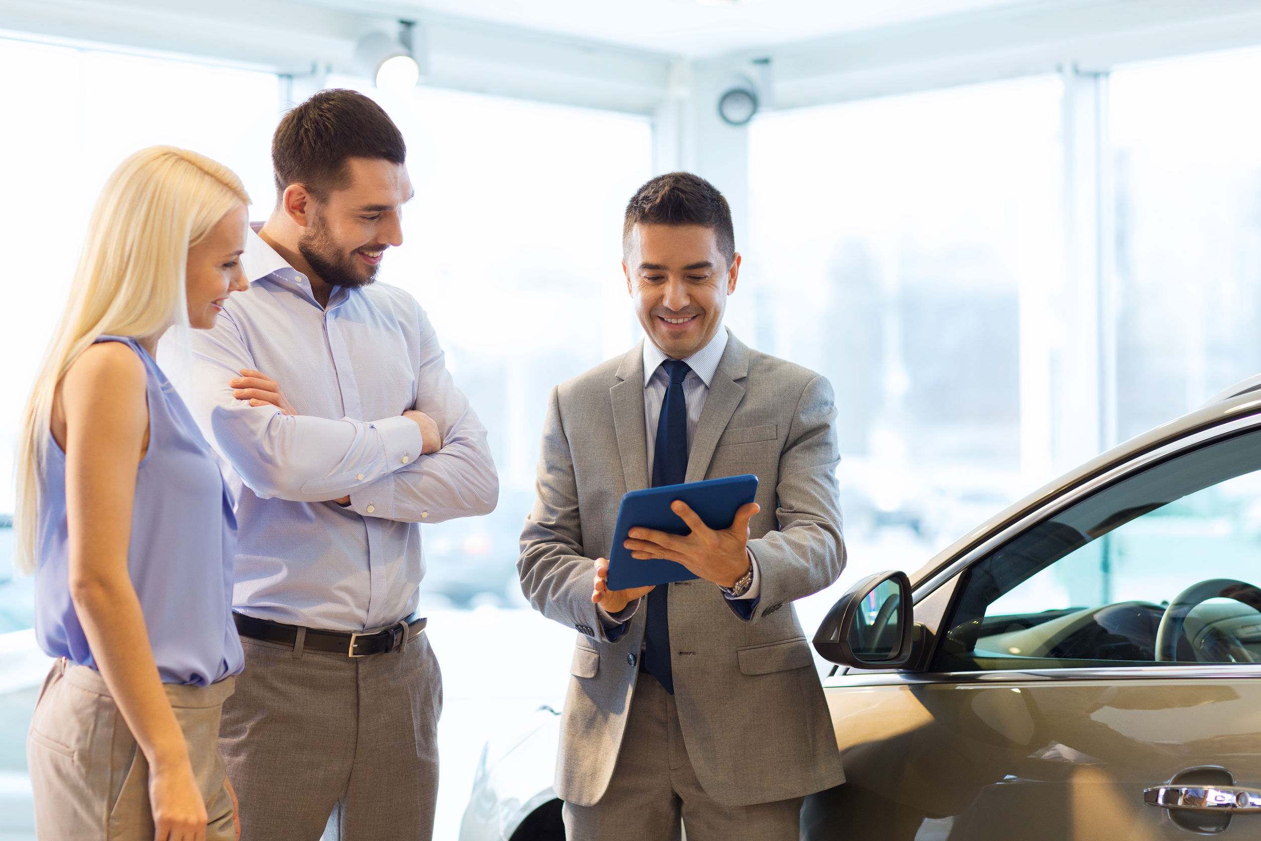 38818354 - auto business, car sale, technology and people concept - happy couple with car dealer in auto show or salon